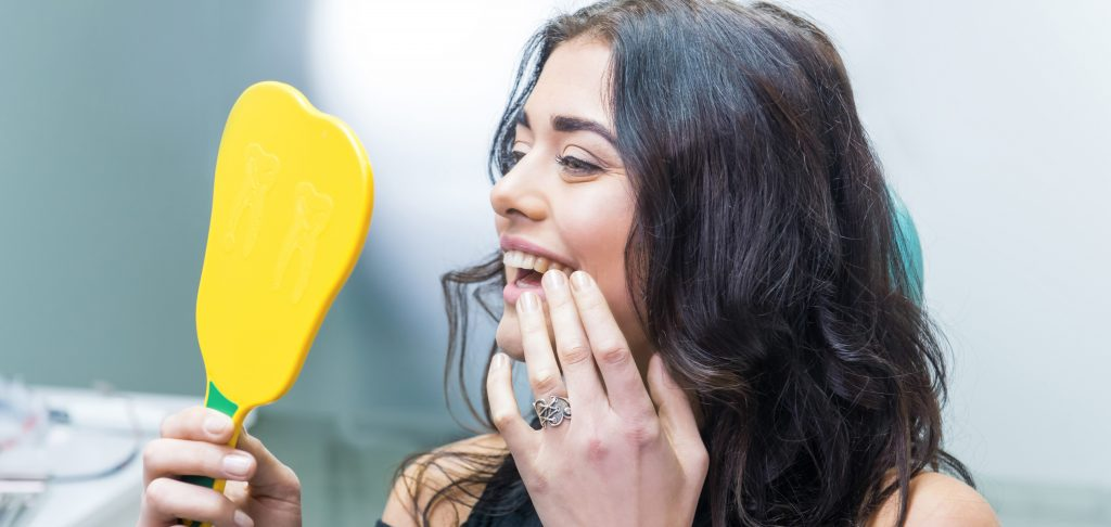 woman looking at her new dental implant for permanent tooth replacement